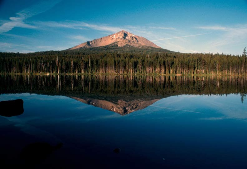 A distant lone peak surrounded by green forest is reflected in a clear blue Lake.