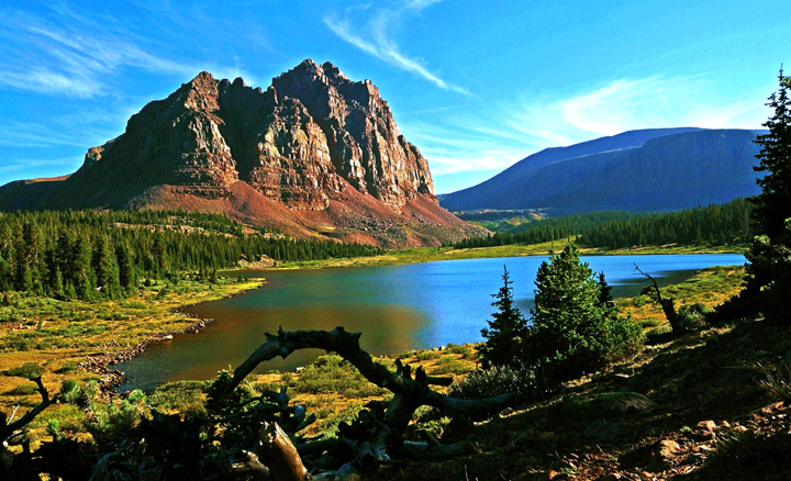 Lower Red Castle Lake surrounder by lush green forest with Red Castle Peak towering above as wispy clouds pass by.