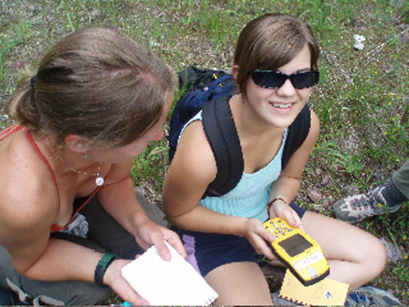 Two female college-age volunteers use a GPS unit to enter information about invasive plant infestations.