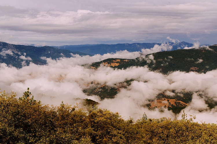 A series of hills with fog-laden valleys.