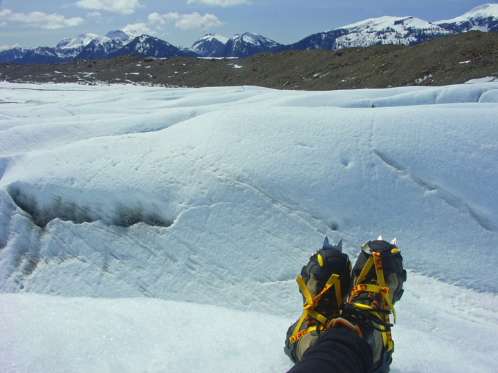 A pair of yellow shoes with crampons can be seen in the foreground.  Beyond the toes stretches a massive snowy glacier, and farther still is a line of snowcapped mountains.