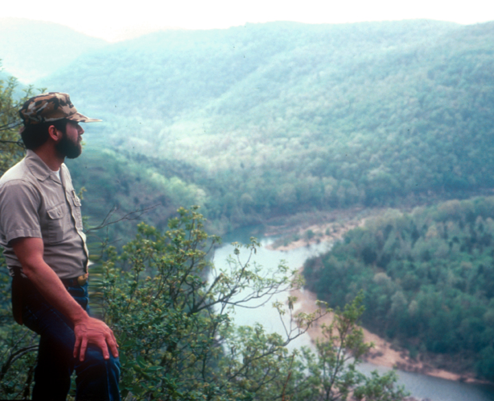 A man looks out over a river and valley.