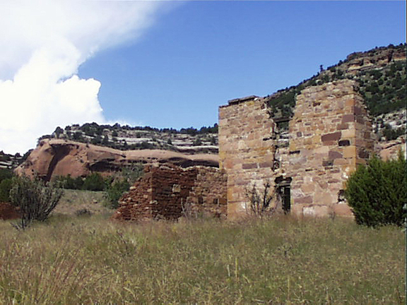 A brick ruin rests in the shadow of a valley rim, nestled in golden grasses and framed by a few scraggly bushes.