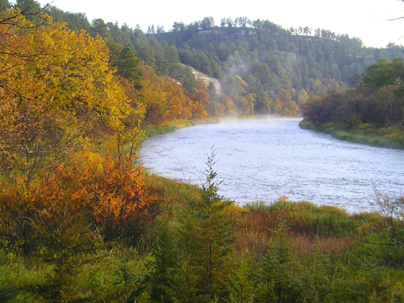 A steaming river curves through a forest painted with all the rich colors of fall: burnished golds, fiery reds and the last greens of summer.