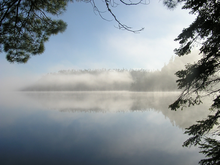 Morning fog settles on Duncan Lake as the sun emerges from the east.