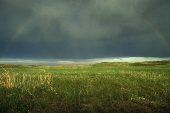 A rainbow arcs over a still storm-bruised sky. Beneath is a green valley, resplendent after a spring rain.