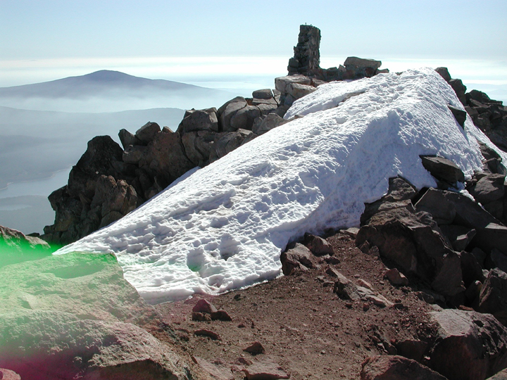 A large patch of snow and ice clings to the rocky top of Old Fire Lookout.