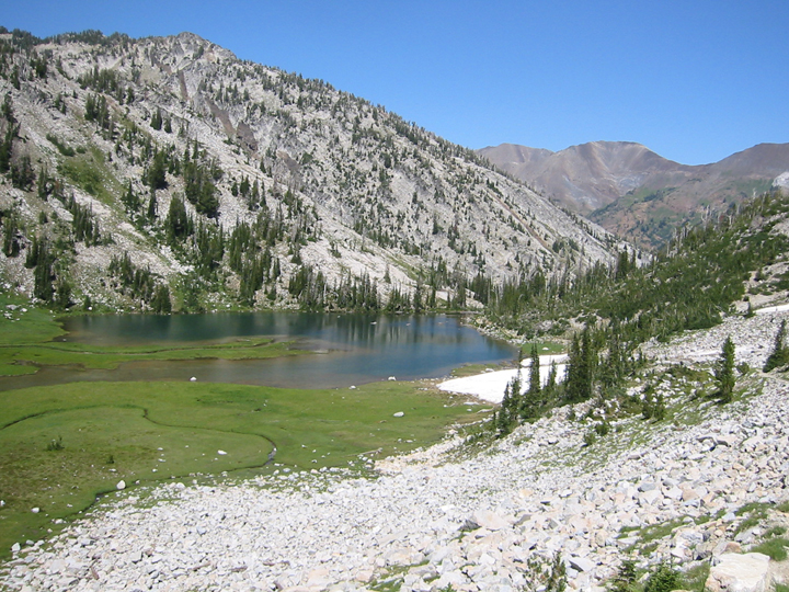 Little Frazier Lake sits at the base of a mountain and the surrounding area is covered in white rocks.
