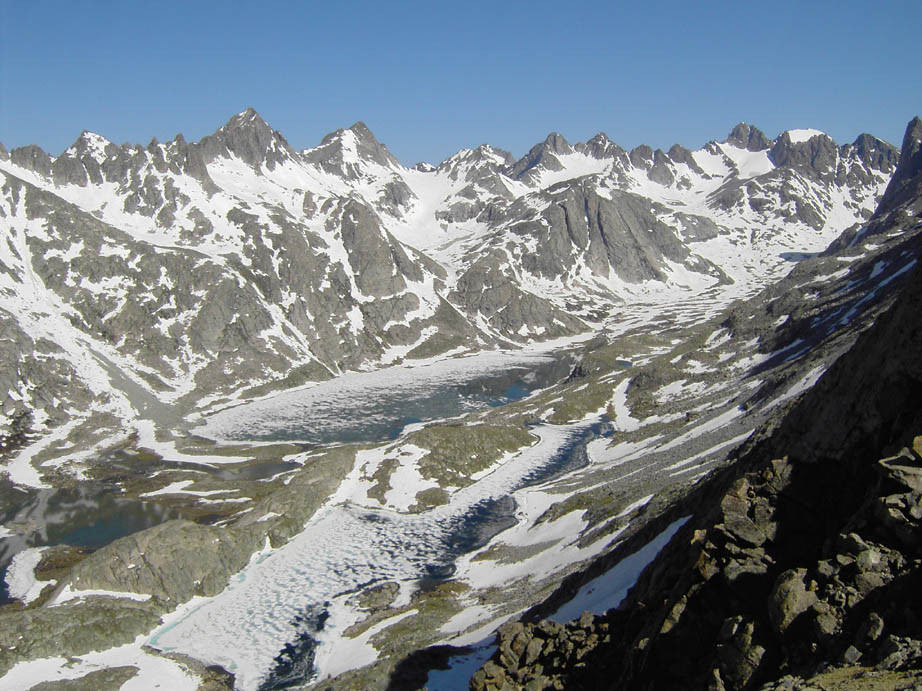 A massive alpine bowl containing two small ice-covered lakes, surrounded by countless jagged peaks of mottled gray rock and white snow.