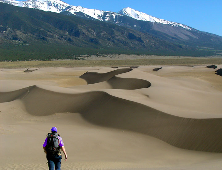 A lone hiker walking towards wind-sculpted sand dunes, with snowcapped mountains rising in the distance under a blue sky.