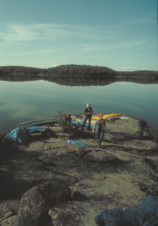 Two canoers walk along a rocky beach, gear spread out around them.  The far of shore is forested.