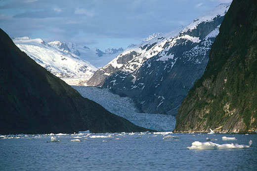 The sky is darkened with clouds. Glacial mountains form the base of this body of water in which icebergs float.