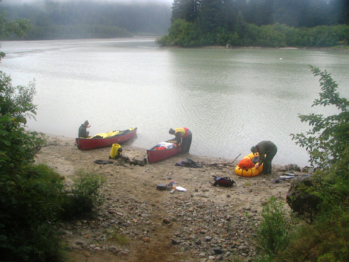 Three paddlers pack supplies into three canoes as they prepare for a float down a large river.