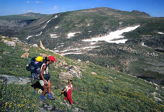 A woman packs a baby on her back while a small child leads the way down a green mountain in the Custer National Forest.