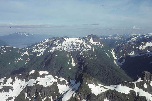 A photo of the peaks in the Admiralty Island National Monument. These peaks are topped with patchs of snow and green trees.