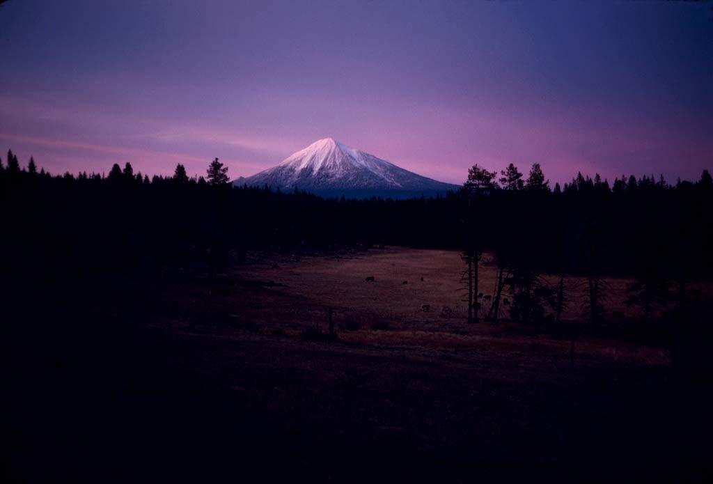 A lone snowcapped peak glows purple in the setting sun.