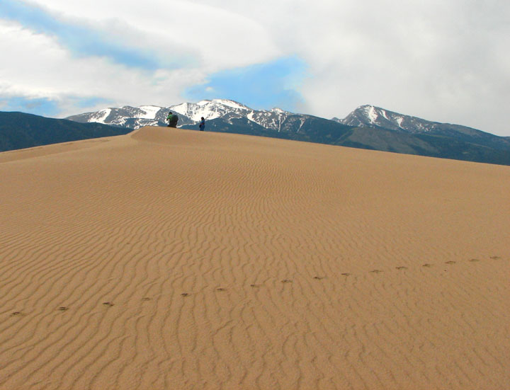 A single set of footprints leading across a rippled dune, with two hikers standing on top viewing distant mountains.