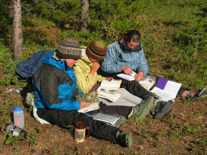 Three students sit on the ground, reading from books during the University of Montana's Wilderness and Civilization Field Studies Fall 2008 Trek.