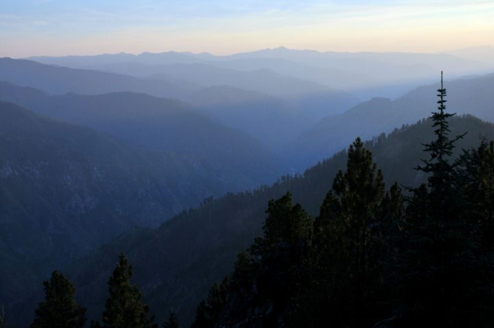 A misty fog hangs over the mountains as the sun sets.