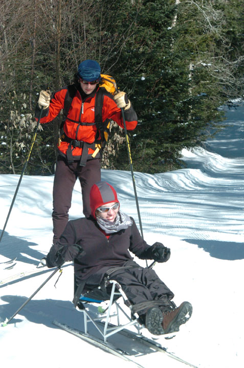 A visitor in a specialized ski-chair is assisted along a section of winter trail through the snow.