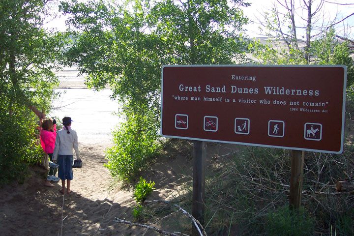 Two visitors in brightly covered jackets pause near a large brown sign alongside a forested trail entering the sand dune area.