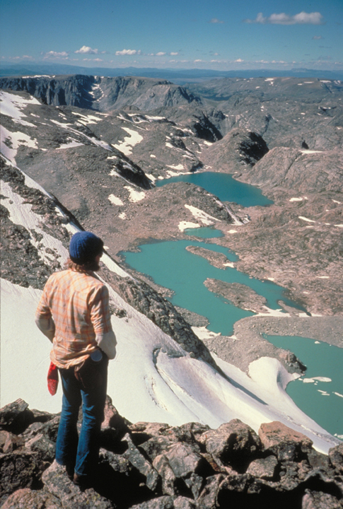 A hiker stands looking over a rocky vista.  Below him, past the snowy slopes, are several blue lakes.
