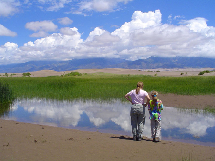A mother and daughter stand at the edge of a small slough, looking out over bright green marsh grass, towards golden sand dunes and mountains in the distance. A blue sky with white puffy clouds reflects off the water.