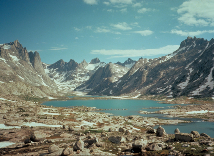 The snowy peaks frame out a rock strewn valley, and the quiet blue lake at the bottom reflects a cloudy sky above.