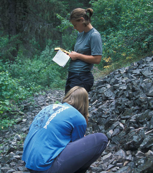 Two volunteers work among a rocky area of a hillside. They use a GPS during University of Montana summer 2007 volunteer weed inventory study.