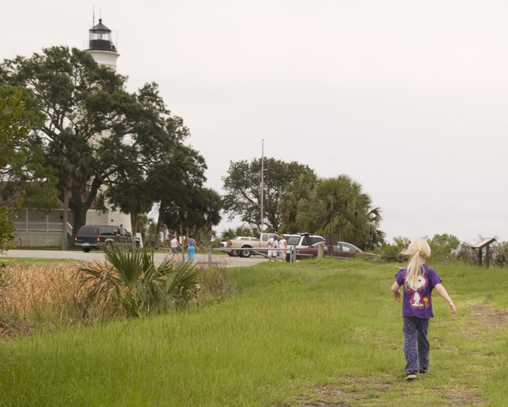 A young girl in a Snoopy shirt heads back towards the white lighthouse.