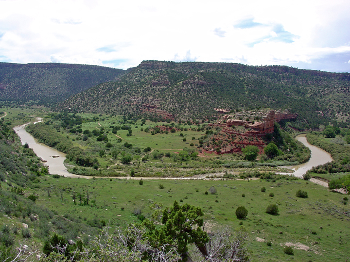 A slow river snakes its way through a green valley.  A red rock formation is the only truly defining characteristic.