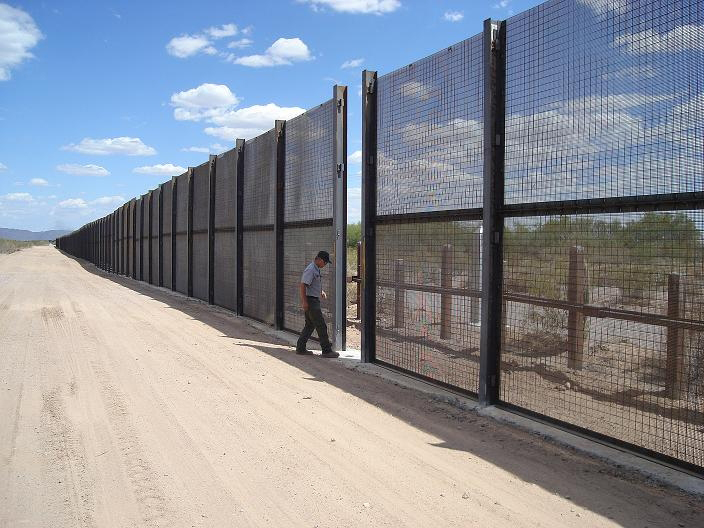 A man walks through a break in a massive pedestrian fence marking the U.S. - Mexico border.