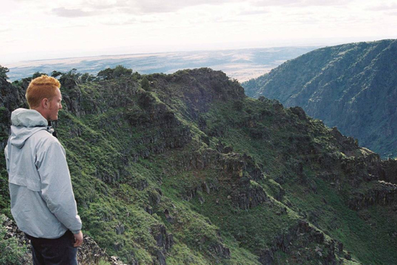 A hiker is caught taking in the green mountainside of a ridge in the Steens Mountain Wilderness.