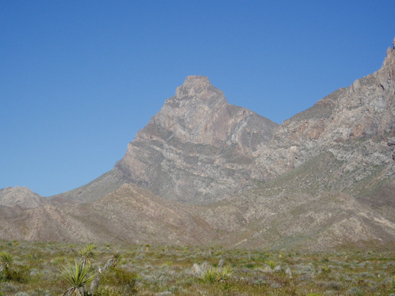 A massive, vertical cliff rises in the background against a brilliant blue sky.  The foreground is an arid area, filled with different types of brush.