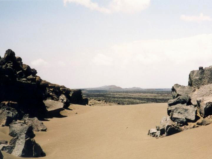 Rocks frame a view of the sweeping sands of the desert with lava beds beyond.
