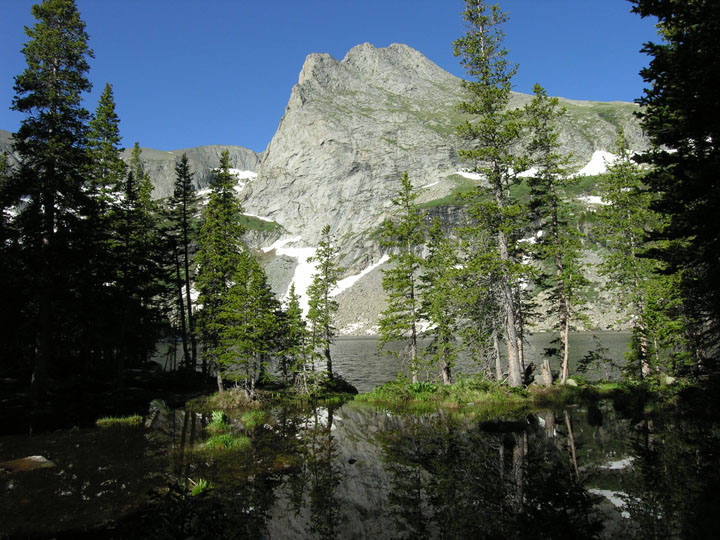 Looking through a thin screen of shadowed trees out over an alpine lake, an exposed rock face rised high towards the blue sky on the far shore.