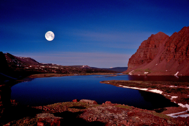 Red Castle Lake with Red Castle Peak to the right sitting underneath a rising full moon.