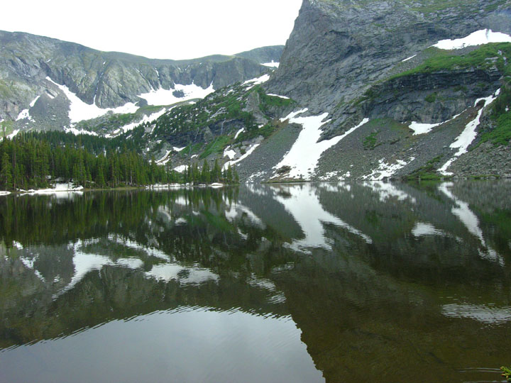 Exposed rock faces laced with snow reflect off the rippled surface of an alpine lake.