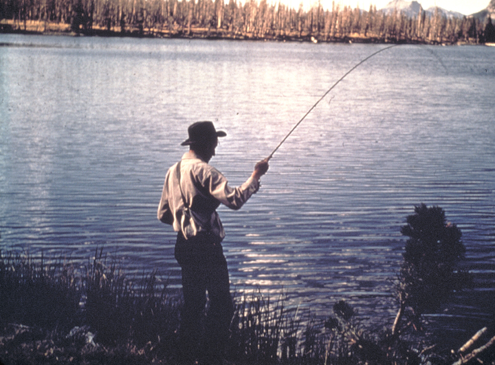 A man in a brimmed hat fishes in the lazy waters of a lake.