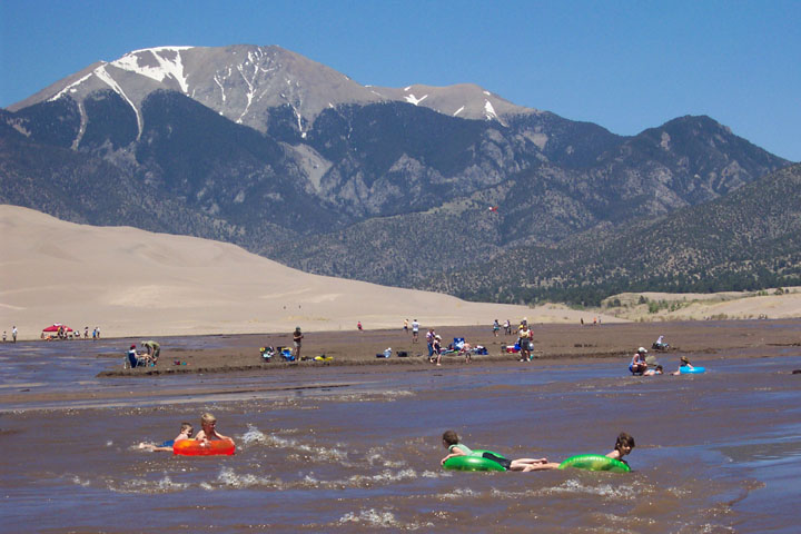 Young children playing in the water on brightly colored innertubes with golden sand dunes and high pointed peaks rising in the distance.