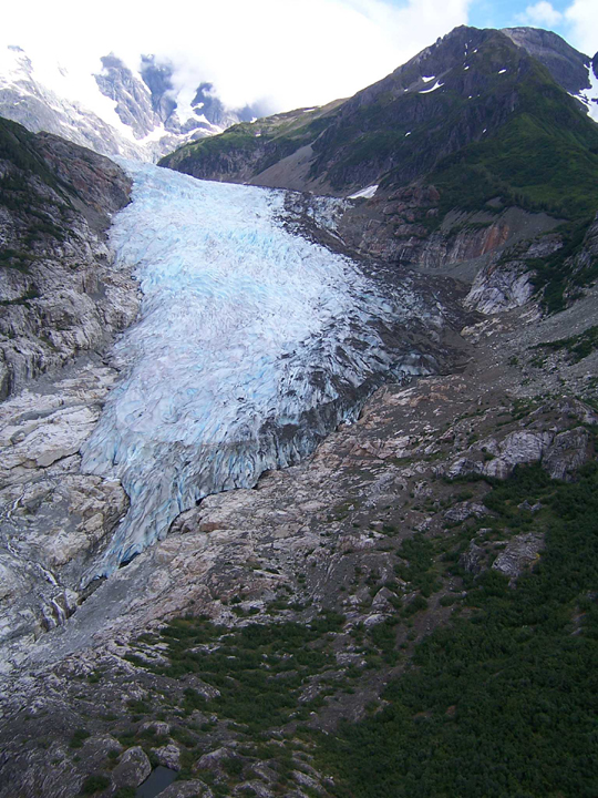 A light blue glacier sits on the steep rocky slope of a large mountain.