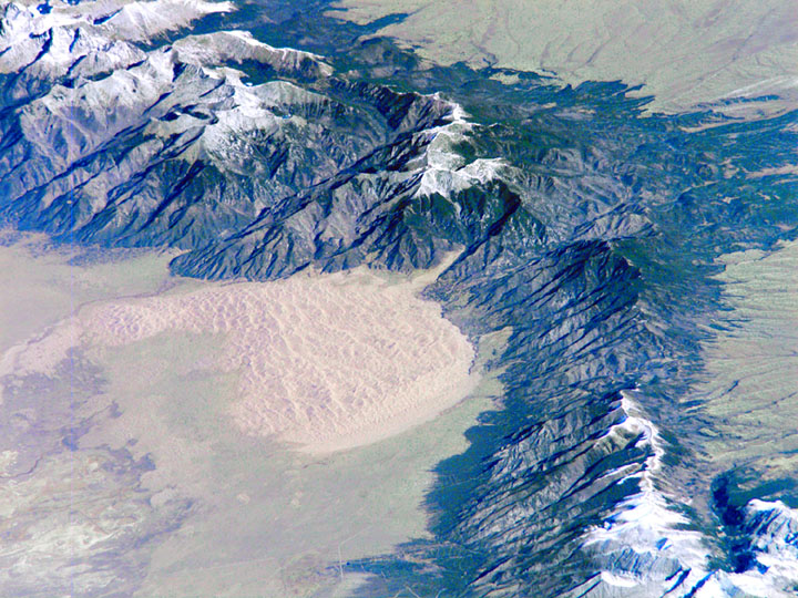 A detailed satellite image showing a tall range of snowcapped mountains and the great golden sand dunes pouring out into the valley beyond.