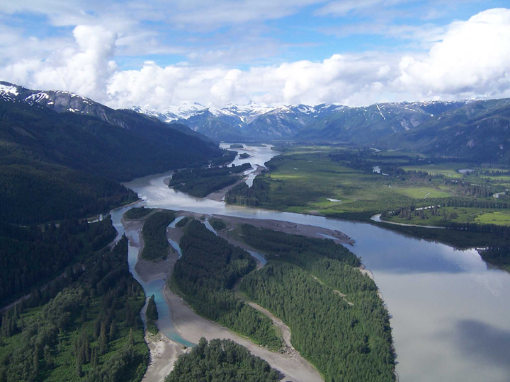 A wide valley with a meandering river running through it with snow-capped mountains in the background.