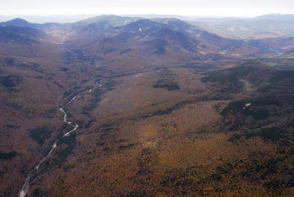 Fall colors stretch over mountainous landscape and the East Branch Pemigewaset River in the White Mountain National Forest.