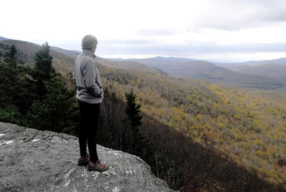 A hiker stands atop a rockface, looking out at the Broadloaf Wilderness which is in the Autumn transition on an overcast day.
