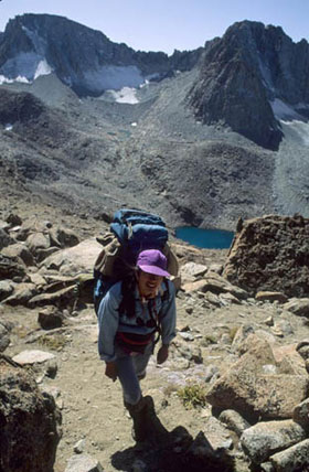 A backpacker hikes up an incline in rocky, dry hills and a small lake sits near the base.