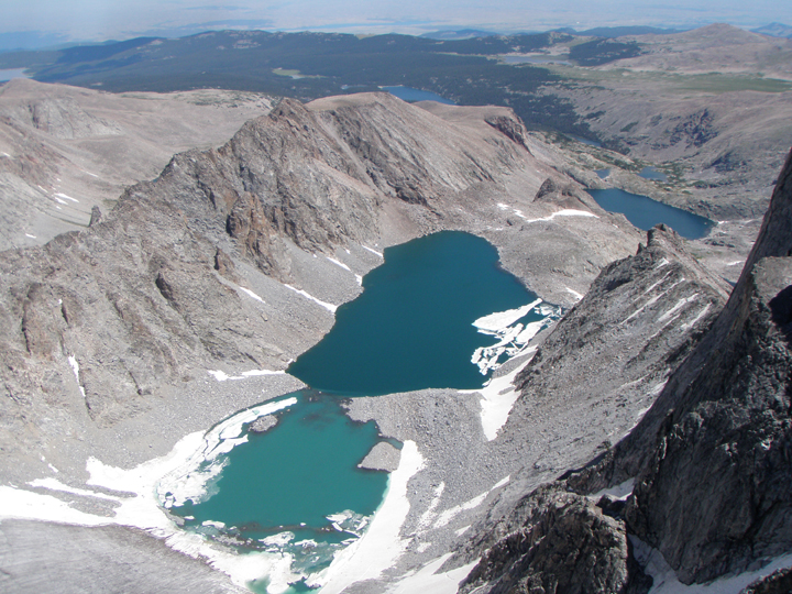 Steep cliffs drop down to a small glacier forming lakes in the valley below.