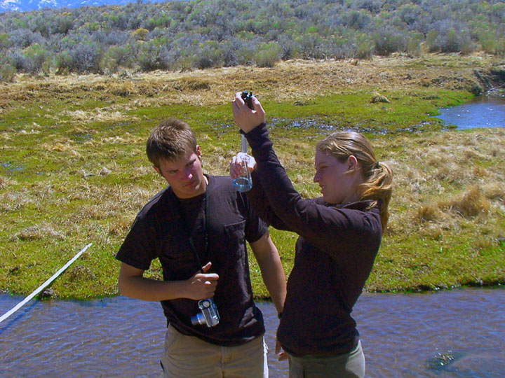 Two college students analyze a water sample in a beaker next to a small stream.