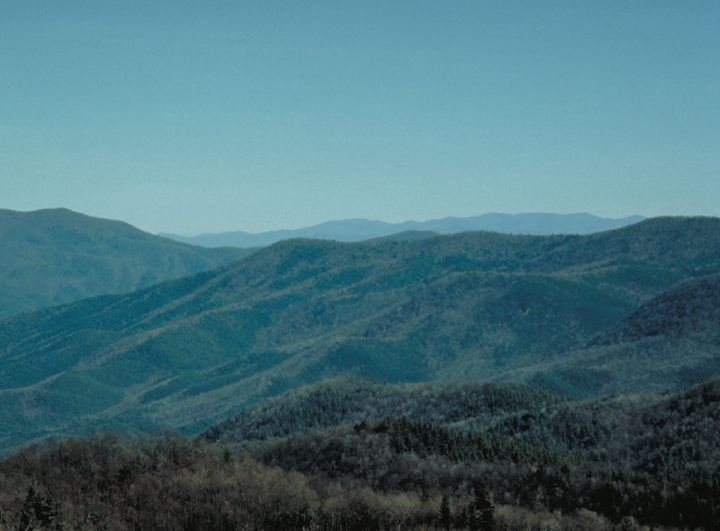 Hills roll off as far as the eye can see, disappearing eventually into the blue mist.