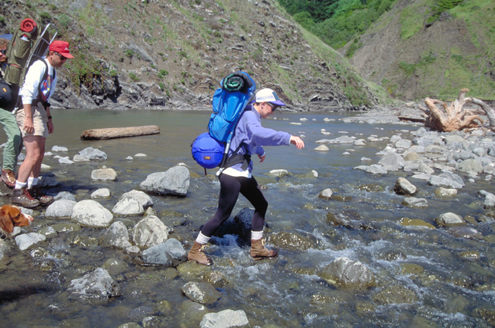 Two backpackers work their way across a rocky stream.